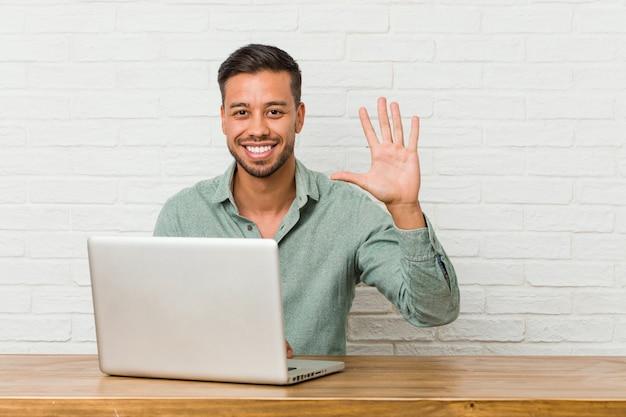 Sitzendes arbeiten des jungen philippinischen mannes mit seinem laptop lächelnde nette darstellende nr. fünf mit den fingern.