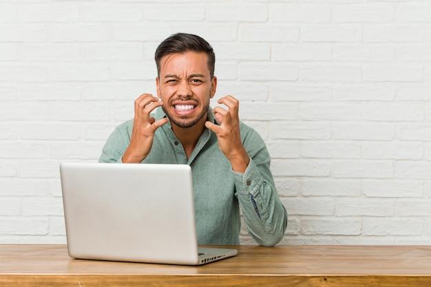 Sitzendes arbeiten des jungen philippinischen mannes mit seinem laptopumkippen, das mit den angespannten händen schreit.
