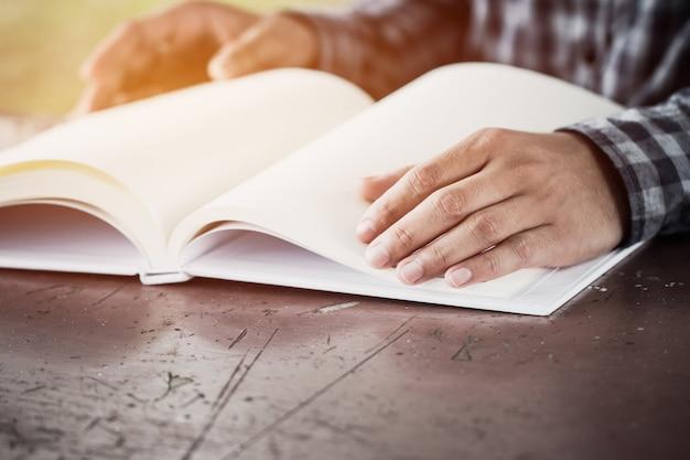Sitzendes buch des glücklichen asiatischen intelligenten mannes leseauf schreibtisch