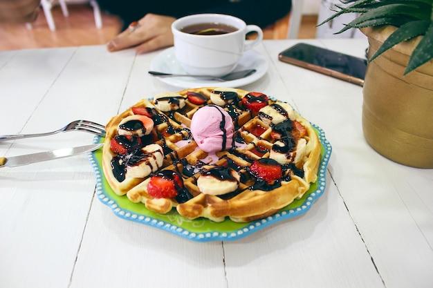Sitzendes caffe des jungen mädchens, das frühstückswaffel mit schokoladensoße, bananenscheiben und erdbeeren auf grüner keramischer platte isst und fotografierte ihr frühstück