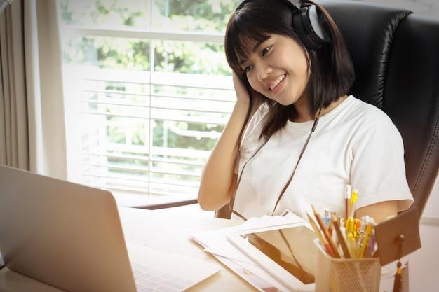 Sitzendes lächeln des schönen asiatischen mädchens scheint so, hörende musik auf kopfhörern glücklich