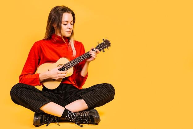 Sitzendes mädchen, welches die ukulele spielt