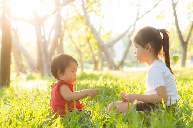 Sitzendes spielen des schönen jungen asiatischen kindes im sommer