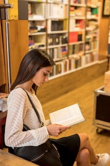 Sitzendes und lesebuch der jungen frau in der bibliothek