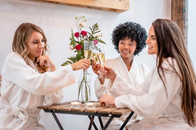 Sitzung im schönheitssalon. drei junge freunde in weißen kitteln sitzen nach der behandlung und trinken champagner.