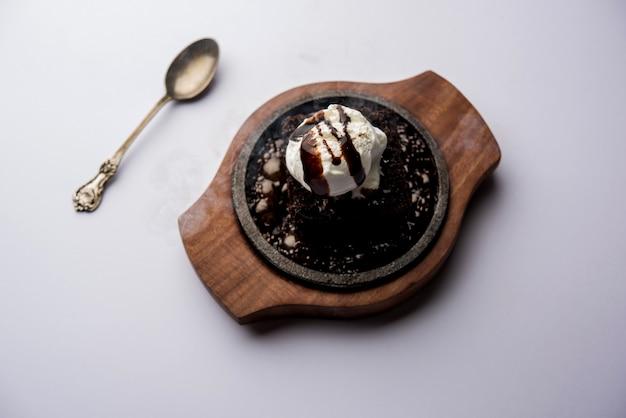 Sizzling chocolate brownie ist ein süßes gericht, das aus einer kugel eiscreme besteht und mit einer großzügigen portion geschmolzener schokolade serviert wird. server heiß. selektiver fokus