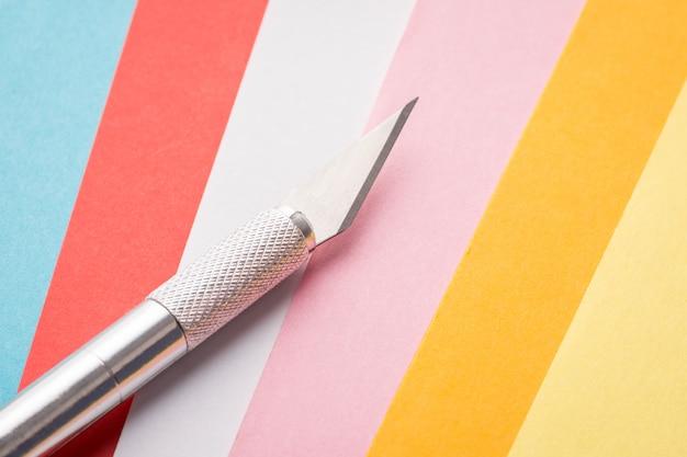 Skalpell für kunstwerke mit papier auf seiten unterschiedlicher farbe
