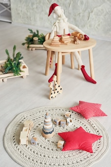 Skandinavische kindermöbel. skandinavisches kinderzimmer mit einem weihnachtsbaum, einer tabelle, einem stuhl und hölzernen pädagogischen spielwaren. der innenraum des kinderzimmers im dachbodenstil.