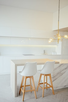 Skandinavische leere klassische moderne luxusküche mit details aus holz, weiß, marmor, neuen stilvollen möbeln und minimalistischem nordischem innendesign. barhocker