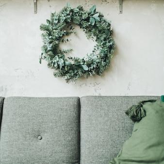Skandinavische wohnung mit weihnachtskranz aus tanne und eukalyptus dekoriert, graue couch mit kissen