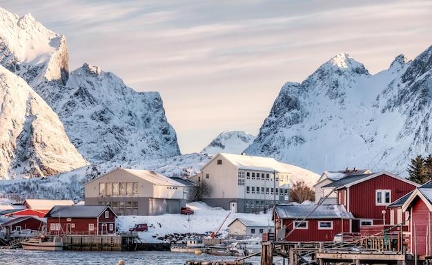 Skandinavisches dorf im schneebedeckten tal am sonnenaufgangmorgen
