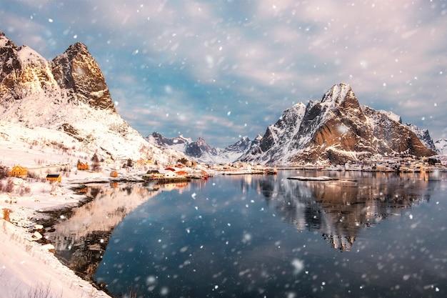 Skandinavisches dorf im schneebedeckten tal auf küstenlinie mit schneefällen am morgen