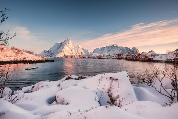 Skandinavisches dorf mit schneebedecktem stapel auf küstenlinie bei sonnenaufgang