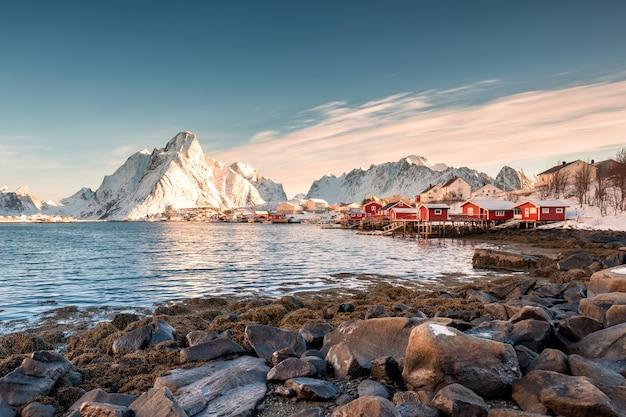 Skandinavisches fischerdorf mit schneebedecktem berg an der küstenlinie