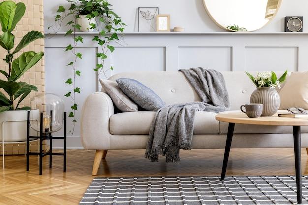 Skandinavisches konzept der wohnzimmereinrichtung mit design-sofa, couchtisch, pflanze im topf, blumen, teppich, plaid, kissen, regal, dekoration und persönlichen accessoires in moderner home-staging.