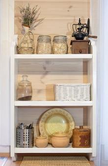 Skandinavisches rustikales weißes offenes holzregal in der küche. mit gläsern, krügen und töpfen