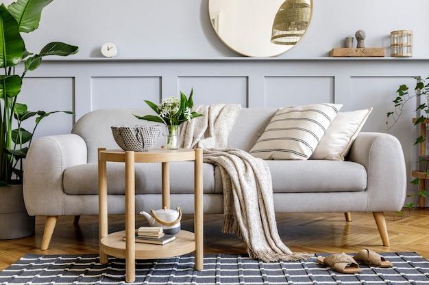 Skandinavisches wohnzimmer mit grauem designsofa, holzcouchtisch, tropischen pflanzen, regal, spiegel, möbeln, kariertem kissen, teekanne, buch und eleganten persönlichen accessoires in der wohnkultur.