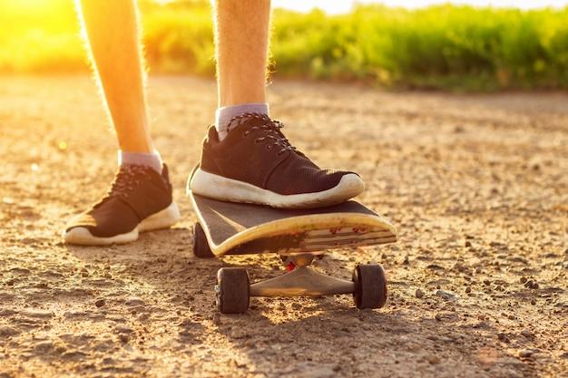 Skateboard fahren auf der straße bei sonnenuntergang, sommerunterhaltung