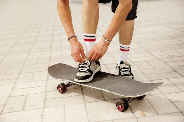 Skateboarder, der sich darauf vorbereitet, an einem wolkigen tag auf der straße der stadt zu fahren. junger mann in turnschuhen und mütze mit einem longboard auf dem asphalt. konzept von freizeitbeschäftigung, sport, extrem, hobby und bewegung.