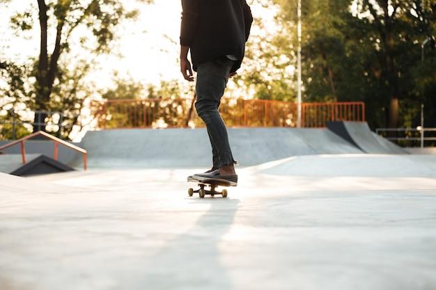Skateboarder des jungen mannes auf skateboard im stadtpark