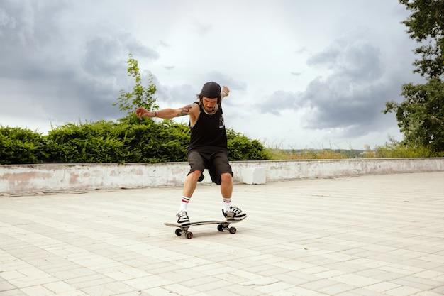 Skateboarder machen an bewölkten tagen einen trick auf der straße der stadt. junger mann in turnschuhen und mütze reiten und longboarding auf dem asphalt. konzept von freizeitbeschäftigung, sport, extrem, hobby und bewegung.