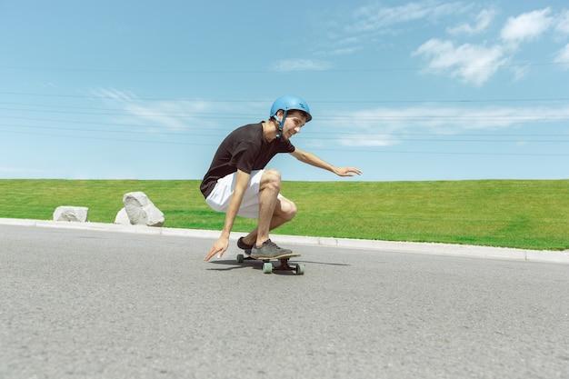 Skateboarder macht an sonnigen tagen einen trick auf der straße der stadt. junger mann im ausrüstungsreiten und longboarden nahe wiese in aktion. konzept von freizeitbeschäftigung, sport, extrem, hobby und bewegung.