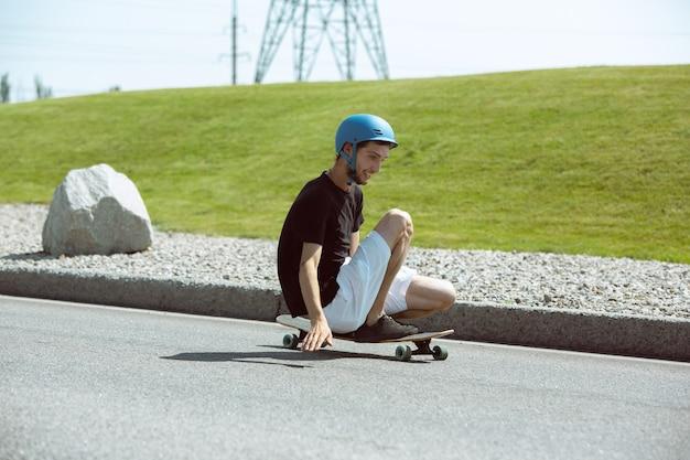 Skateboarder macht an sonnigen tagen einen trick auf der straße der stadt. junger mann in ausrüstungsreiten und longboarding auf dem asphalt in aktion. konzept von freizeitbeschäftigung, sport, extrem, hobby und bewegung.