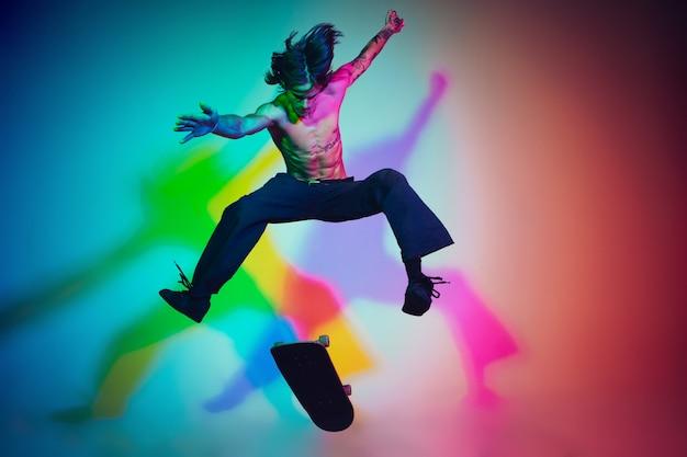 Skateboarder macht einen trick isoliert im studio