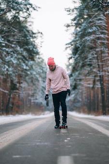 Skateboarder steht auf der straße mitten im wald, umgeben von schnee
