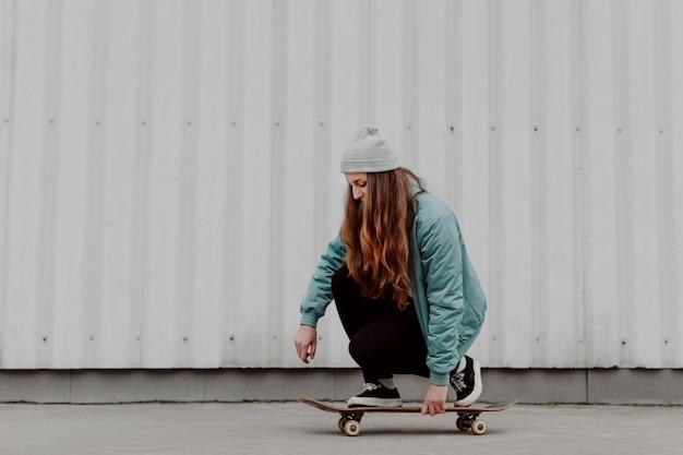 Skateboarderin, die ihren schlittschuh in der stadt reitet
