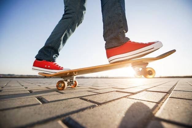 Skater, der ein skateboard reitet. ansicht einer person, die auf seinem rochen trägt beiläufige kleidung reitet