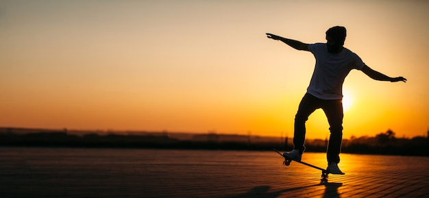 Skater-hipster-mann, der auf einem brett auf einer stadtstraße während des sonnenuntergangs reitet