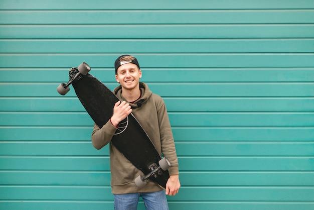 Skater in freizeitkleidung steht mit einem longboard in der hand vor dem hintergrund einer türkisfarbenen hellen wand