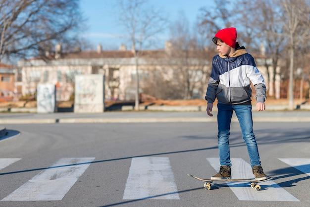 Skater-jugendlicher, der einen hut trägt, der auf der straße verschalt