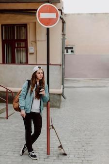 Skater mädchen hält eine tasse kaffee
