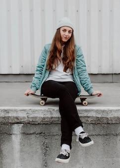 Skater-mädchen in der stadt, die auf dem schlittschuh sitzt