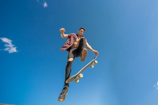 Skater mit skateboard macht trick die luft