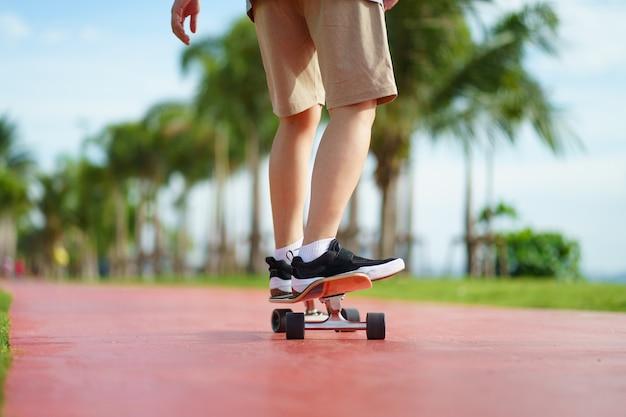 Skater schließen oben von den beinen mit palmenhintergrund