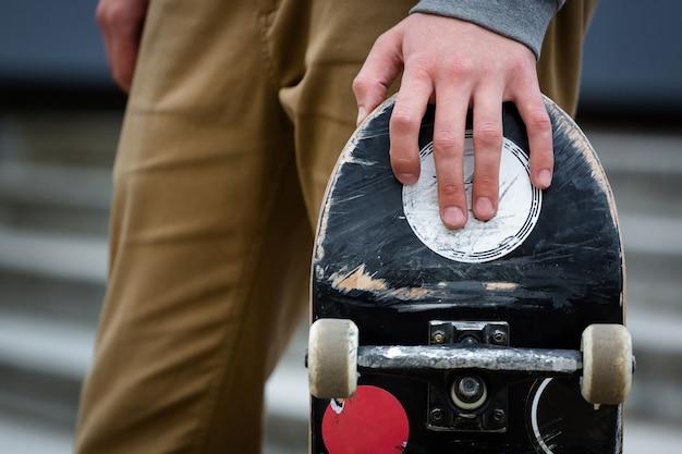 Skaterhand, die skateboarddeck in einer städtischen umgebung im freien hält