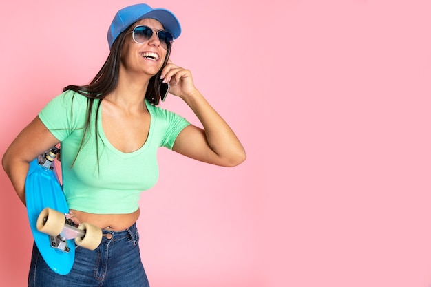 Skating mädchen ist glücklich und lächelnd am telefon in jeans und eine kappe auf dem kopf gekleidet