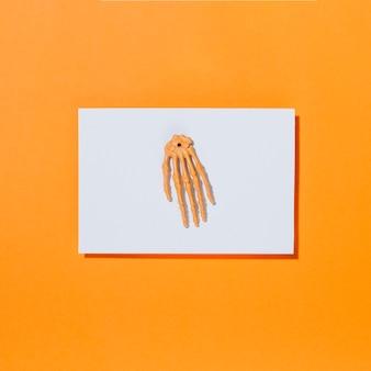 Skeleton knochenhand auf stück weißbuch