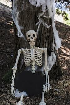 Skelett, das nahe baum sitzt und tablette in der fleckform hält