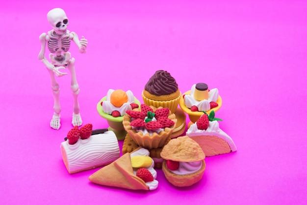 Skelett stehend und bäckerei, genießen sie das essen bis zum tod mit süßen desserts.