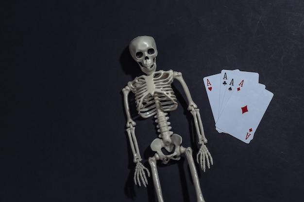 Skelett und vier asse auf schwarzem hintergrund. spielsucht. Premium Fotos