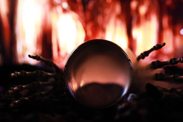 Skelett-zombie-hand steigt aus einem friedhof - halloween. mysteriöse magische ballvorhersagen und rauch auf dunkler szene. wahrsagerin, geisteskraft, vorhersagekonzept. mysteriöser hintergrund