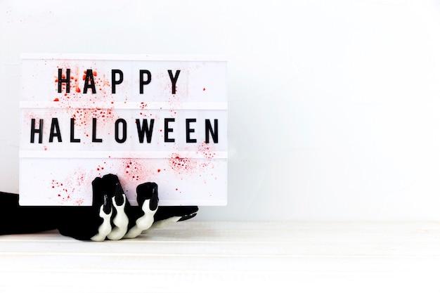 Skeletthand, die brett mit glücklichem halloween-schreiben hält