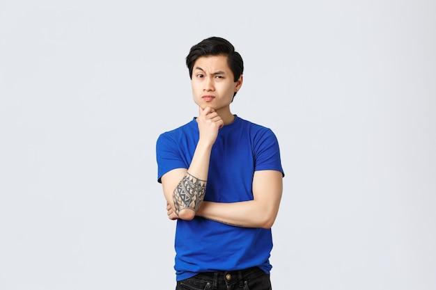 Skeptisch, ernst aussehender asiatischer mann in blauem t-shirt mit tätowierungen, der person misstrauisch zuhört, die stirn runzelt, das kinn nachdenklich berührt, nachdenkt, eine entscheidung trifft, unglauben ausdrückt, grauer hintergrund