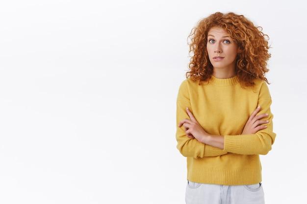 Skeptisch hübsche rothaarige frau in gelbem pullover, mit lockigem haar, verschränkter brust, augenbrauen hochziehen und ungläubig anstarren, jemanden lügen hören, wertend über weiße wand schauen