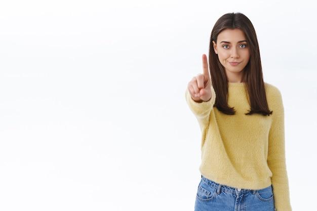 Skeptisch und ernst aussehende junge selbstbewusste frau verbieten handlungen, verbieten etwas, schimpfen die person mit missbilligendem ausdruck, schütteln den finger in der stopp-geste