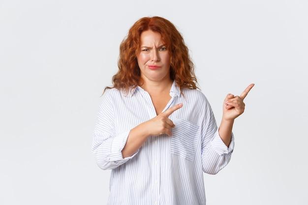 Skeptisch und unzufrieden, klagt die rothaarige frau mittleren alters unzufrieden